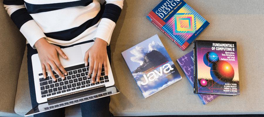 Foto di una ragazza che studia come diventare un programmatore informtico davanti con un laptop
