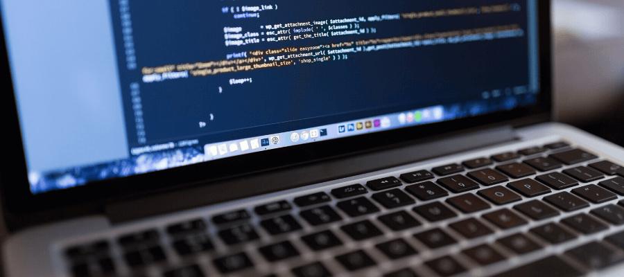 Dettaglio del computer portatile di un programmatore, che ha aperta un'app di coding