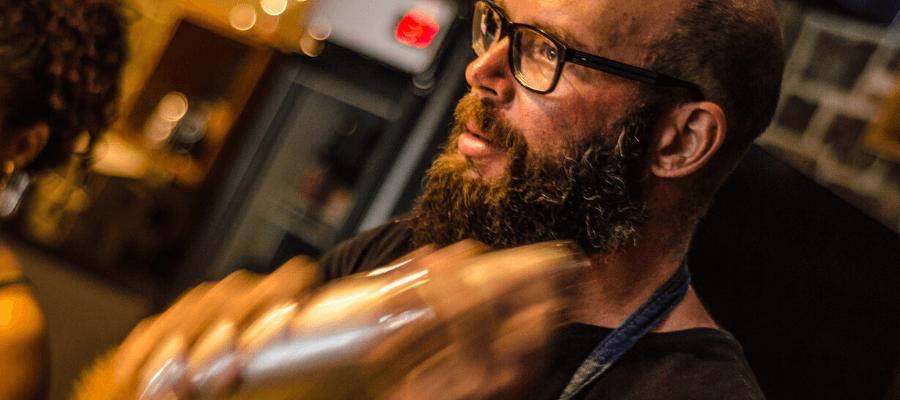 un bartender che prepara un cocktail con l'uso dello shaker