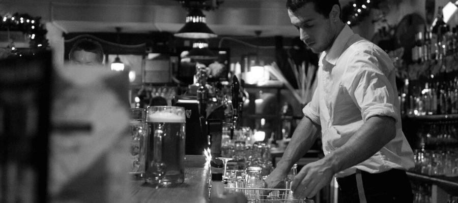 Il barista di un locale dietro al bancone mentre sistema i bicchieri puliti