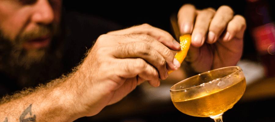le mani di un barman che aggiungono uno spicchio d'arancia a un coktail