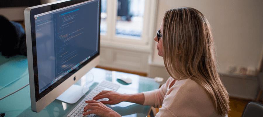 Una programmatrice informatica che lavora seduta alla scrivania e con un PC della Apple