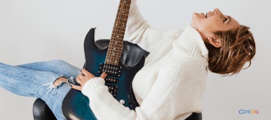 Una ragazza seduta che suona una chitarra e si diverte