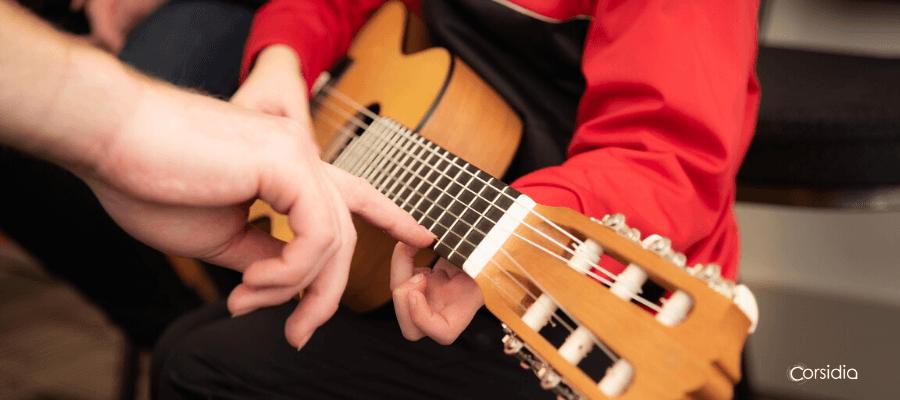 Dettaglio di una chitarra suonata da un giovane allievo che viene corretto dal maestro
