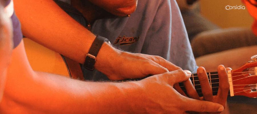 Le mani di un insegnante di chitarra guidano quelle dell'allievo, mentre insegna gli accordi