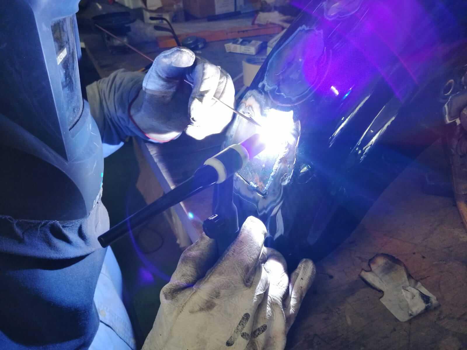 Saldatore professionista mentre ripara il parafango di una motocicletta con saldatura TIG